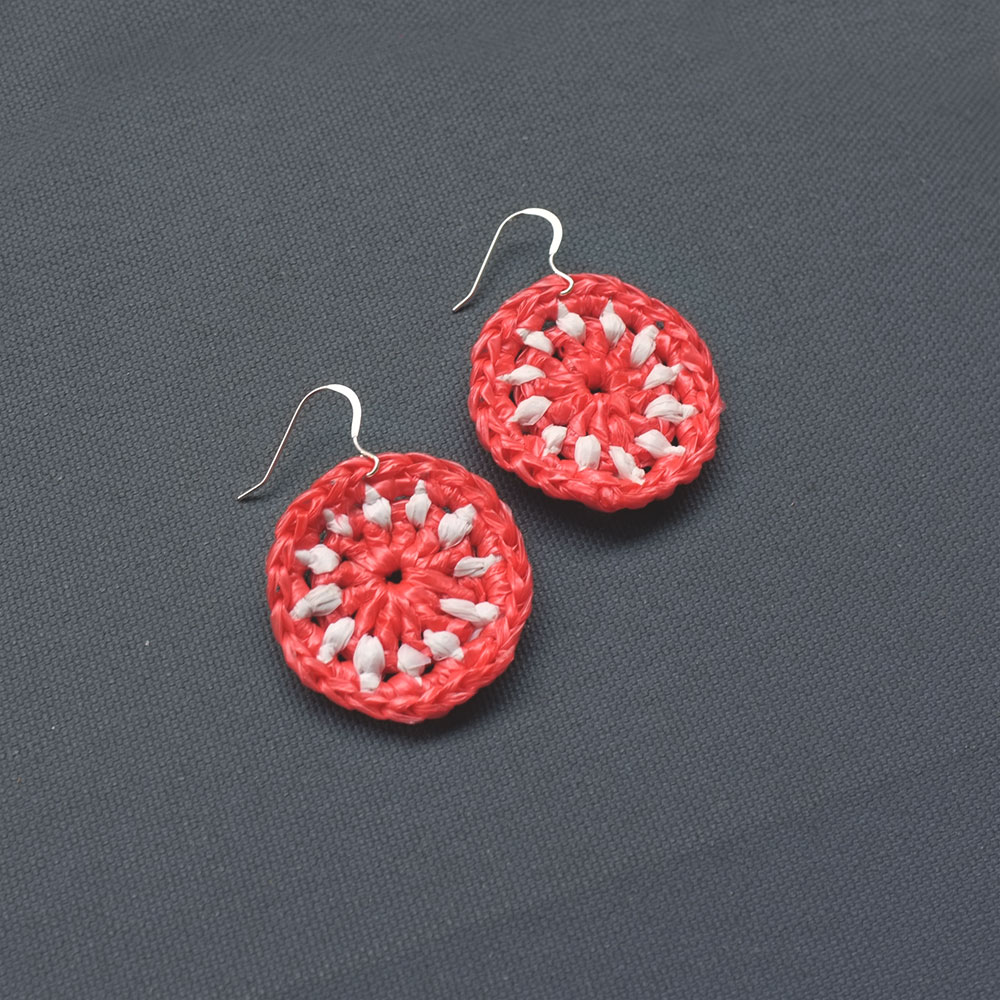 These circular earrings crocheted with discarded plastic bags.